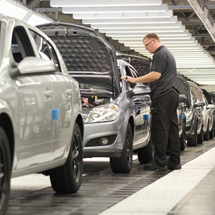 man checking cars on an assembly line in a manuracturing plant