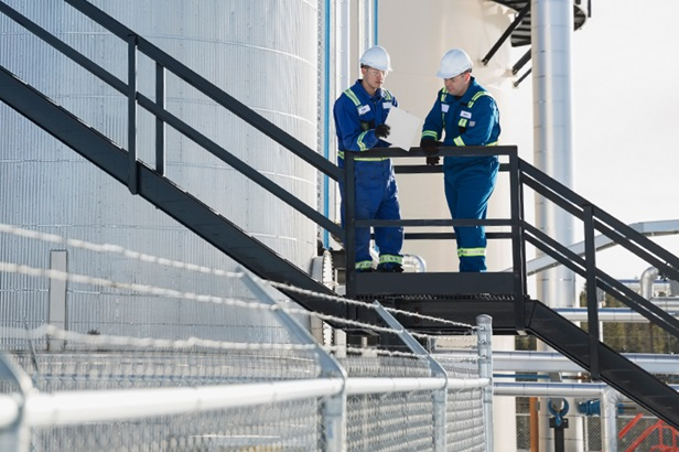two worker talking outside on a platform at a gas plant